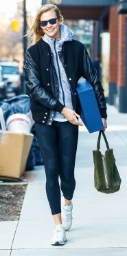 Karlie Kloss has that wind blown look carrying large box and tote walking to her car